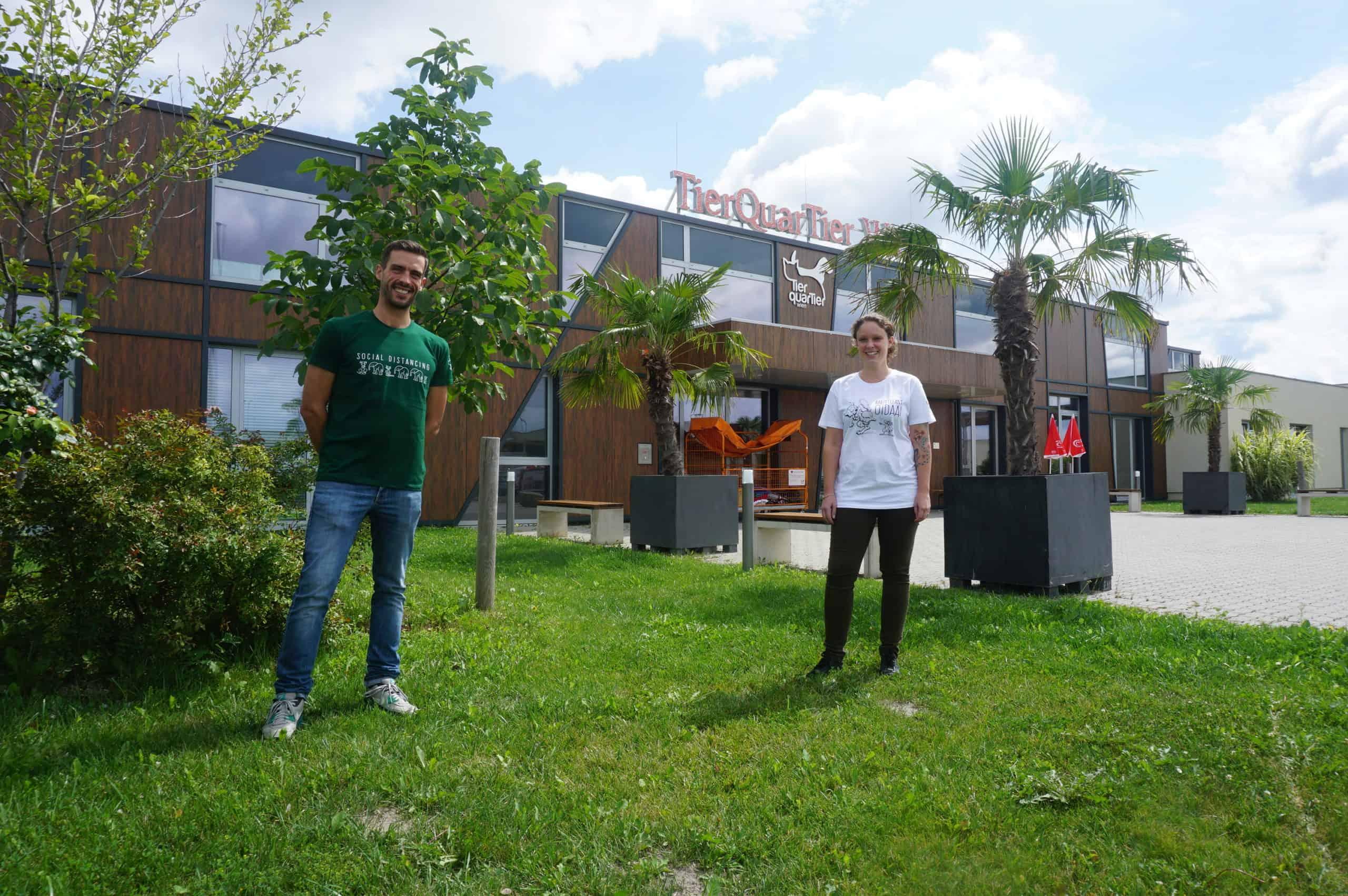 Zwei Mitarbeiter des TierQuarTiers Wien stehen auf einer Wiese. Sie tragen die T-Shirts.