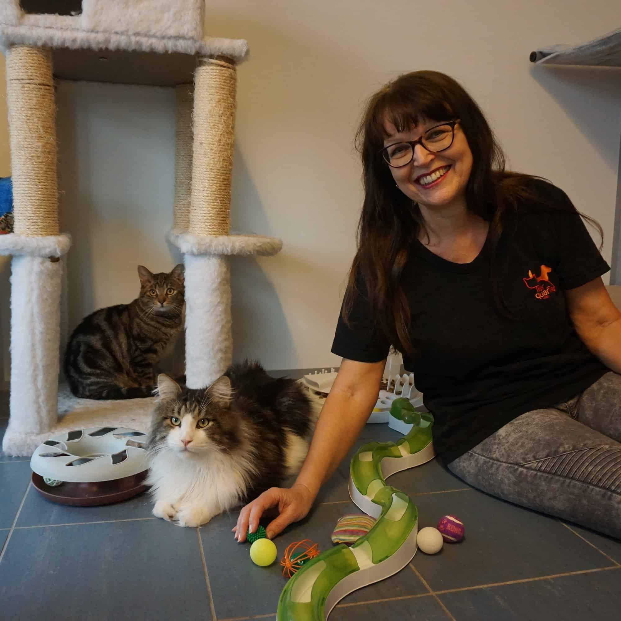 Eine Frau sitzt auf dem Boden und streichelt eine Katze.